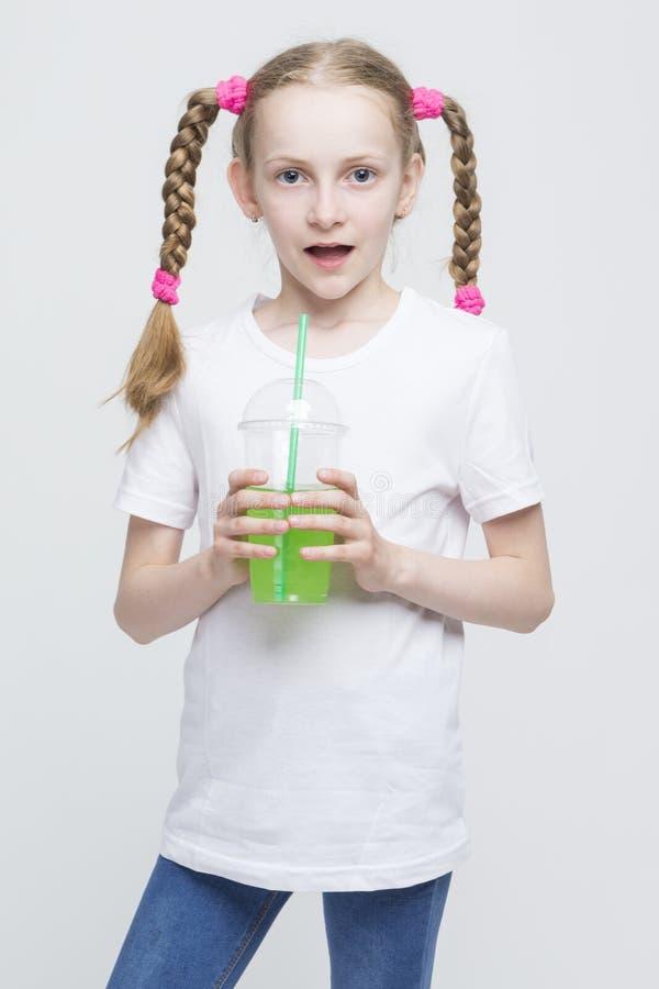 Vrij Kaukasisch Blond Meisje met de Lange Kop van de Vlechtenholding en het Drinken Groen Sap royalty-vrije stock foto