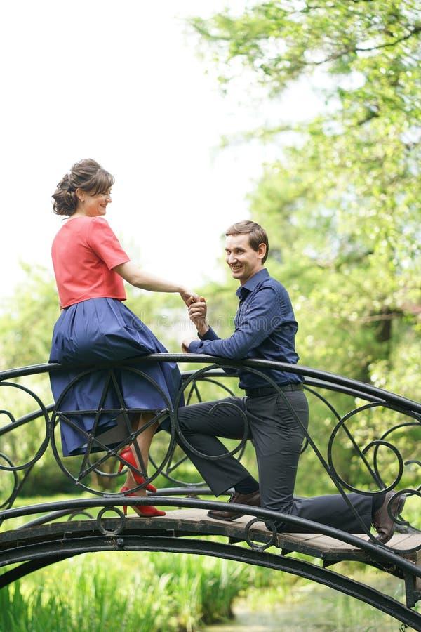 Vrij Kaukasisch liefdepaar die in het groene de zomerpark lopen, die glimlachen, kussen en omhelzingen hebben stock foto's