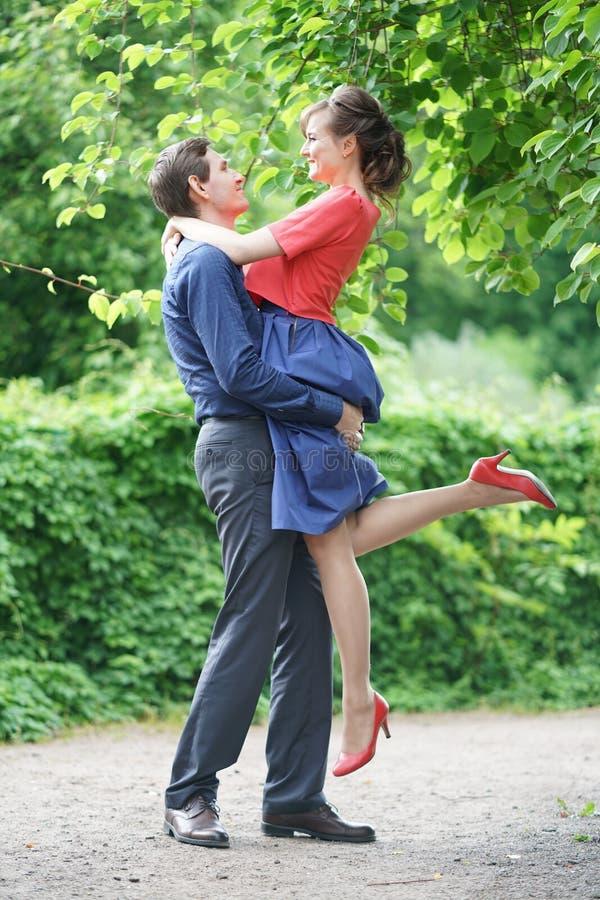 Vrij Kaukasisch liefdepaar die in het groene de zomerpark lopen, die glimlachen, kussen en omhelzingen hebben royalty-vrije stock fotografie
