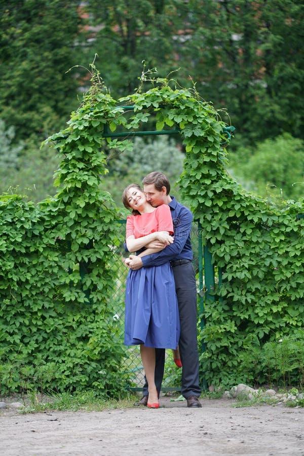 Vrij Kaukasisch liefdepaar die in het groene de zomerpark lopen, die glimlachen, kussen en omhelzingen hebben royalty-vrije stock afbeeldingen