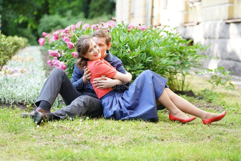 Vrij Kaukasisch liefdepaar die in het groene de zomerpark lopen, die glimlachen, kussen en omhelzingen hebben stock afbeeldingen