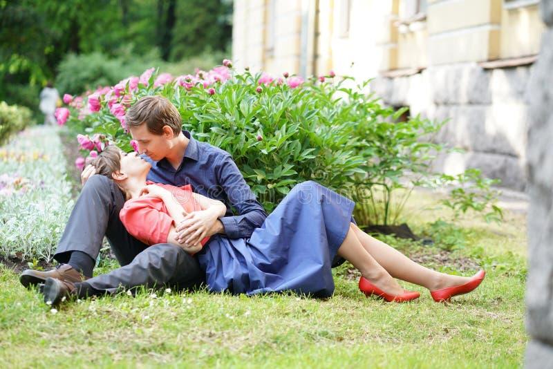 Vrij Kaukasisch liefdepaar die in het groene de zomerpark lopen, die glimlachen, kussen en omhelzingen hebben royalty-vrije stock foto's
