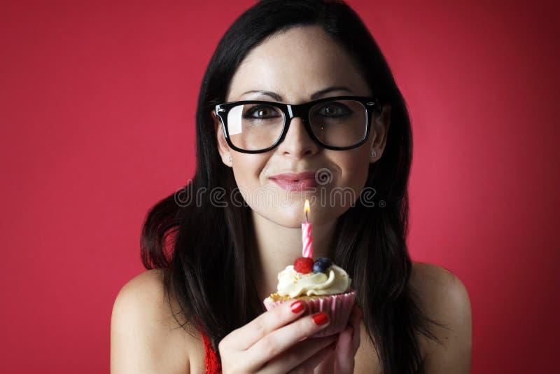 Vrij Kaukasisch meisje met glazen die uit kaars op haar kopcake blazen op rode achtergrond royalty-vrije stock foto's