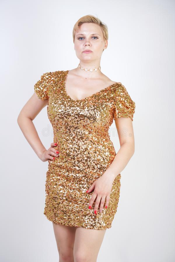 Vrij Kaukasisch plus het meisje van het grootteblonde met plus groottelichaam en grote borsten die gouden korte strakke partijkle royalty-vrije stock fotografie