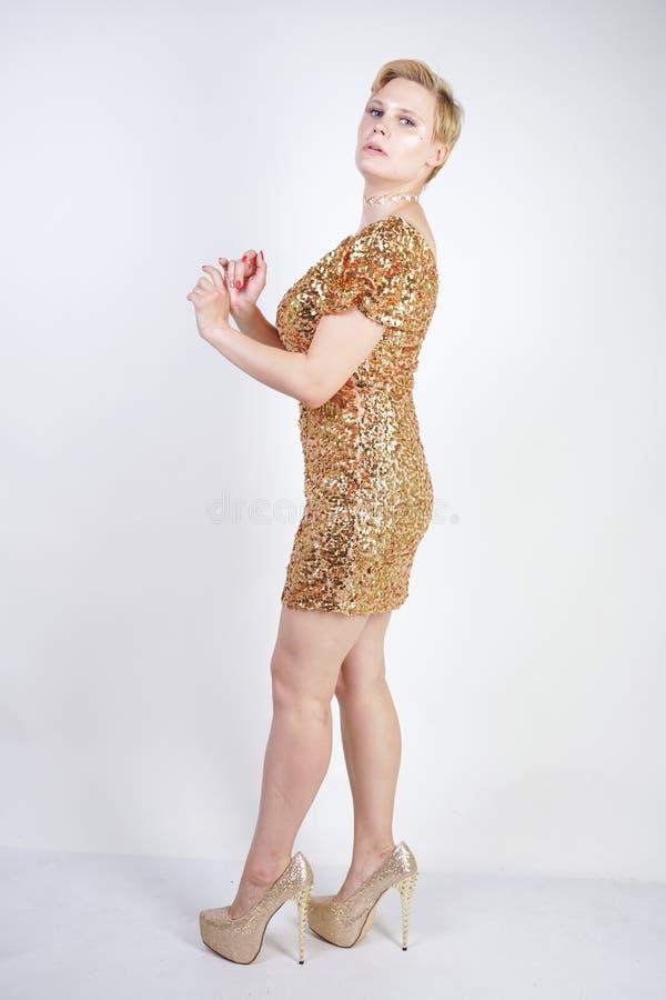 Vrij Kaukasisch plus het meisje van het grootteblonde met plus groottelichaam en grote borsten die gouden korte strakke partijkle royalty-vrije stock foto