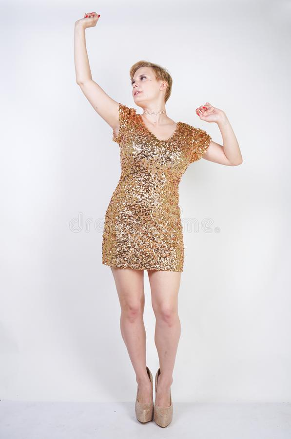 Vrij Kaukasisch plus het meisje van het grootteblonde met plus groottelichaam en grote borsten die gouden korte strakke partijkle stock afbeelding