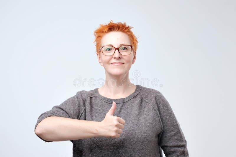 Vrij Kaukasische rijpe vrouw met rood haar die duimen tonen die omhoog over een witte achtergrond wordt geïsoleerd royalty-vrije stock fotografie