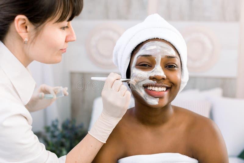 Vrij Kaukasische vrouw Cosmetologist die masker op gezicht van Afrikaans-Amerikaanse vrouw in witte handdoek in kuuroordsalon toe stock afbeeldingen