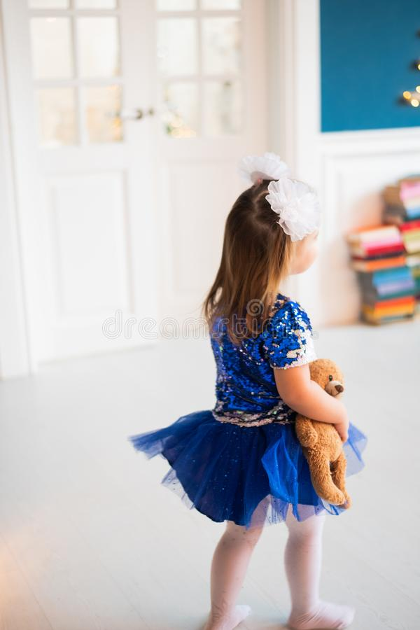 Vrij klein meisje in mooie blauwe kleding die en haar stuk speelgoed achteruitgaan houden royalty-vrije stock afbeeldingen