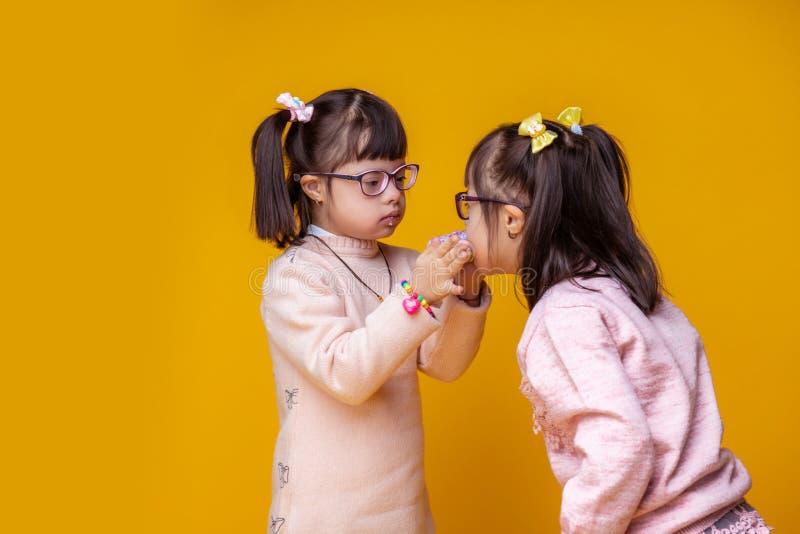 Vrij kleine tweelingen met geestelijke wanorde die elkaar voeden stock afbeelding