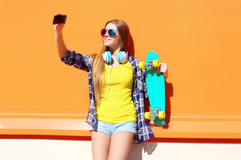 Vrij koel glimlachend meisje in zonnebril met skateboard die beeld zelfportret op smartphone nemen royalty-vrije stock fotografie