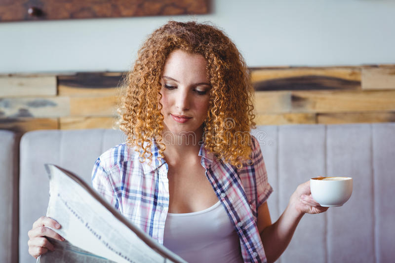 Vrij krullend haarmeisje die kop van koffie hebben en krant lezen stock afbeeldingen