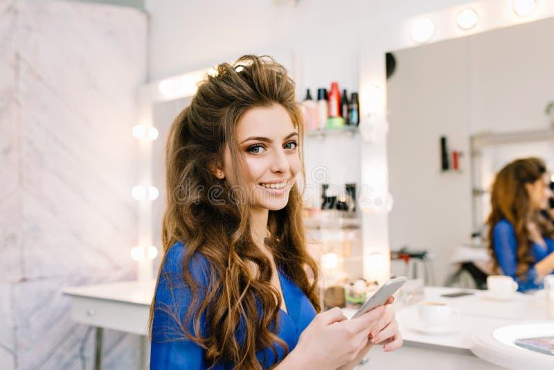 Vrij leuke jonge vrouw die met lang donkerbruin haar aan camera in kappersalon glimlachen Schoonheid, die aan partij voorbereidin royalty-vrije stock foto's