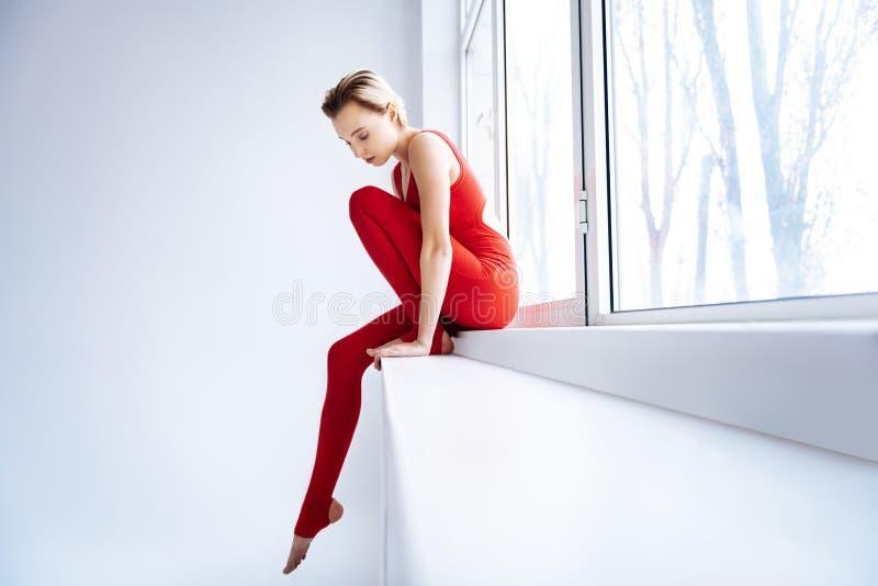 Vrij magere vrouwenzitting op de vensterbank stock foto's