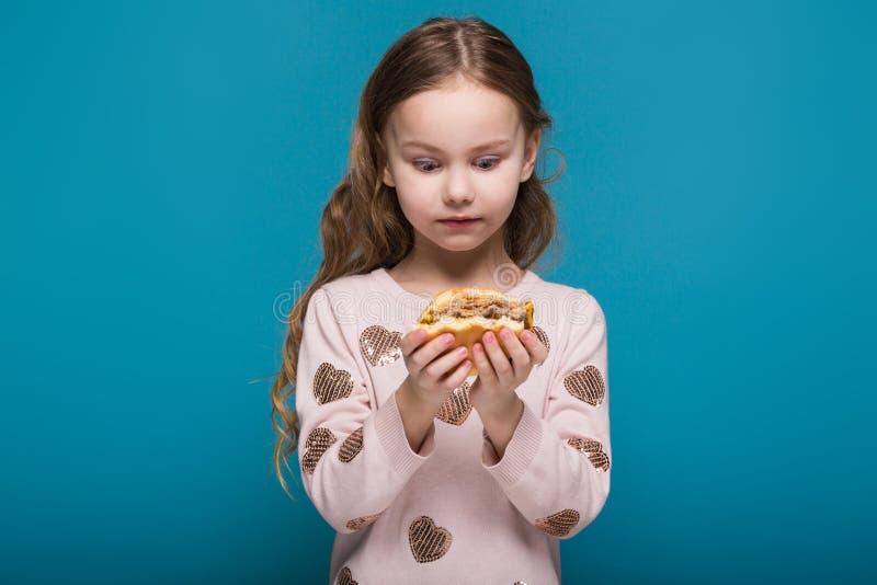 Vrij, meisje in sweater met donkerbruine haargreep een hamburger royalty-vrije stock foto