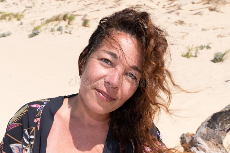 Vrij midden oude vrouwen krullende haren in wind in de zomervakantie van het zandstrand stock afbeelding