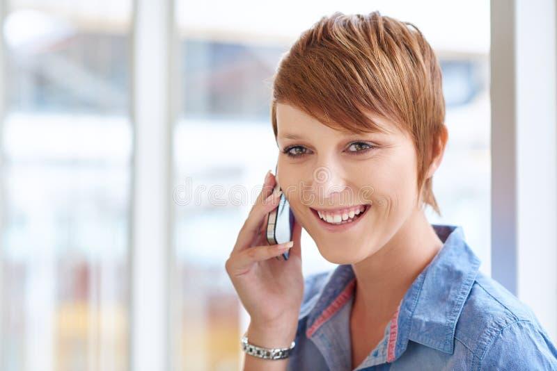 Vrij moderne vrouw die terwijl het luisteren aan haar mobiele telefoon glimlachen stock foto