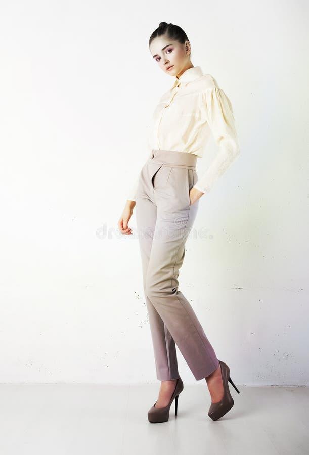 Vrij modieus meisje in witte broeken en blouse royalty-vrije stock afbeeldingen