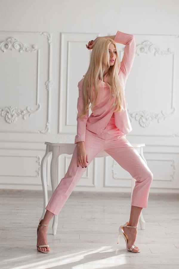 Vrij modieuze jonge modelvrouw in modieuze roze kleren met schoenen die in de studio stellen stock foto