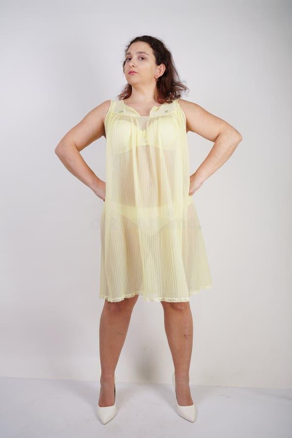Vrij mollig meisje modieus geel ondergoed en liefdes dragen haar lichaam en zelf die mollige vrouw in lingerie op witte backgroun royalty-vrije stock foto's