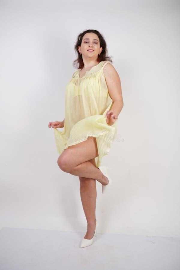 Vrij mollig meisje modieus geel ondergoed en liefdes dragen haar lichaam en zelf die mollige vrouw in lingerie op witte backgroun royalty-vrije stock foto