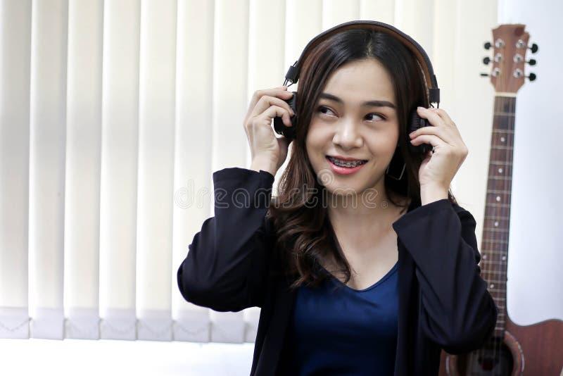 Vrij mooie Aziatische vrouw die hoofdtelefoon en het luisteren muziek draagt stock foto's