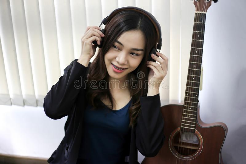 Vrij mooie Aziatische vrouw die hoofdtelefoon en het luisteren muziek dragen royalty-vrije stock afbeeldingen