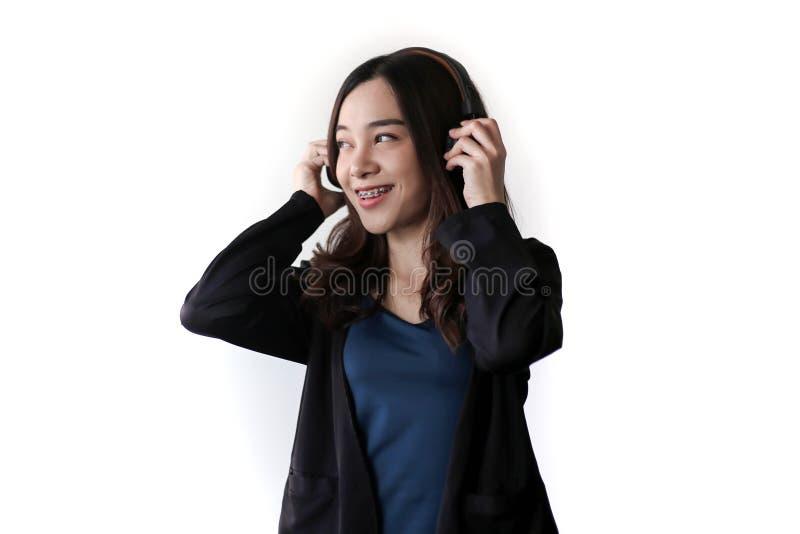 Vrij mooie Aziatische vrouw die hoofdtelefoon en het luisteren muziek op witte achtergrond dragen royalty-vrije stock fotografie