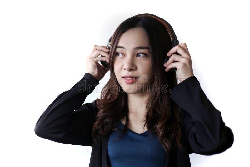 Vrij mooie Aziatische vrouw die hoofdtelefoon en het luisteren muziek op witte achtergrond dragen royalty-vrije stock afbeelding
