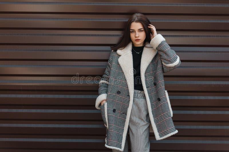 Vrij mooie jonge donkerbruine vrouw in een zwarte t-shirt in een modieus grijs geruit jasje in het uitstekende broek stellen royalty-vrije stock afbeeldingen