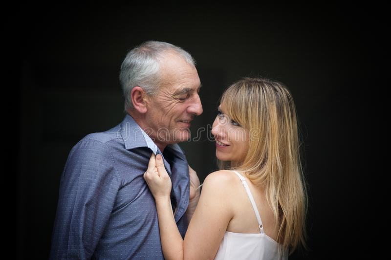 Vrij Mooie Jonge Vrouw die Zijn Bejaarde Echtgenoot koesteren en hem met Hartstocht bekijken Het Concept van het leeftijdsverschi royalty-vrije stock afbeelding