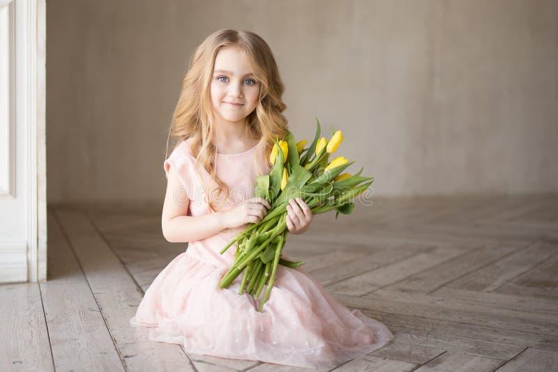 Vrij mooie meisjeszitting op de vloer met gele bloemen tulpen en het glimlachen Binnenfoto Het meisje van Nice De ruimte van het  royalty-vrije stock afbeelding
