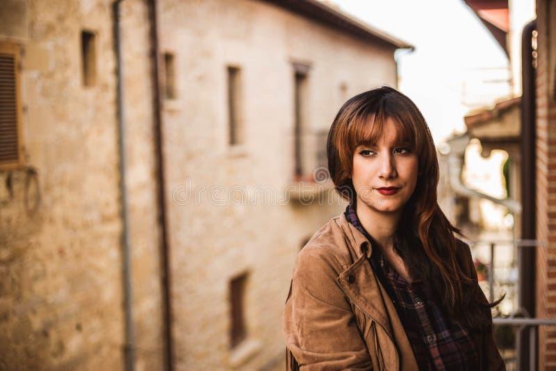 Vrij nadenkende jonge vrouw op het balkon in een oude stad royalty-vrije stock afbeelding