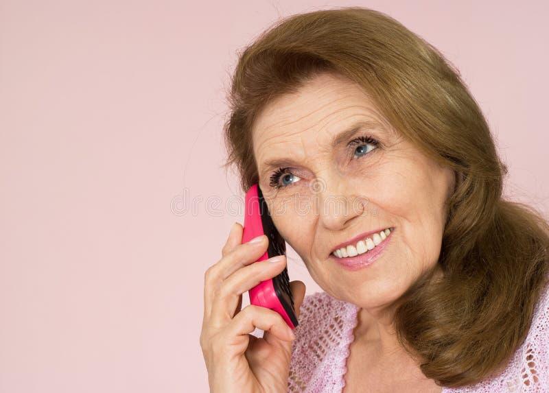 Vrij oude vrouw met een telefoon royalty-vrije stock afbeelding
