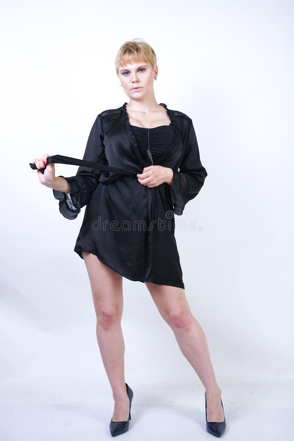 Vrij plus groottevrouw met kort haar en mollig curvy lichaam die retro bodysuit ondergoed dragen en op witte studio stellen backg stock foto