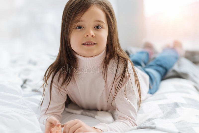 Vrij prettig meisje die op het bed liggen stock foto