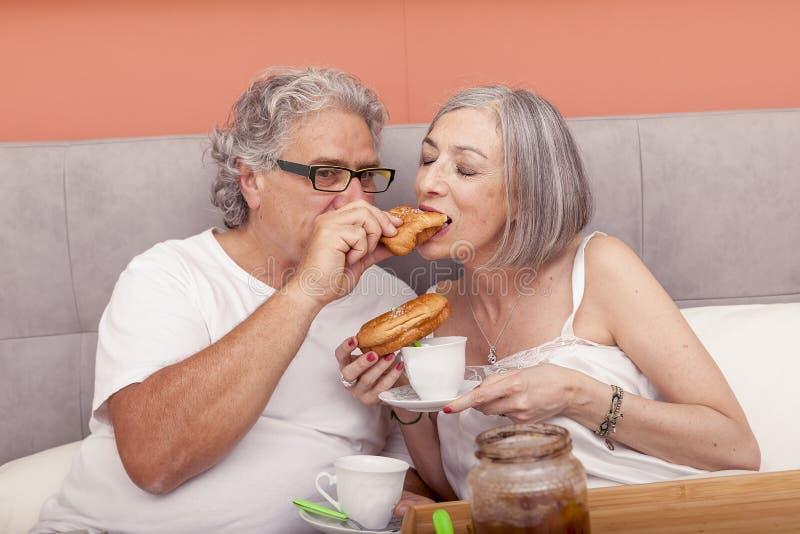 Vrij rijp paar die pret in het bed hebben terwijl het eten van ontbijt stock fotografie