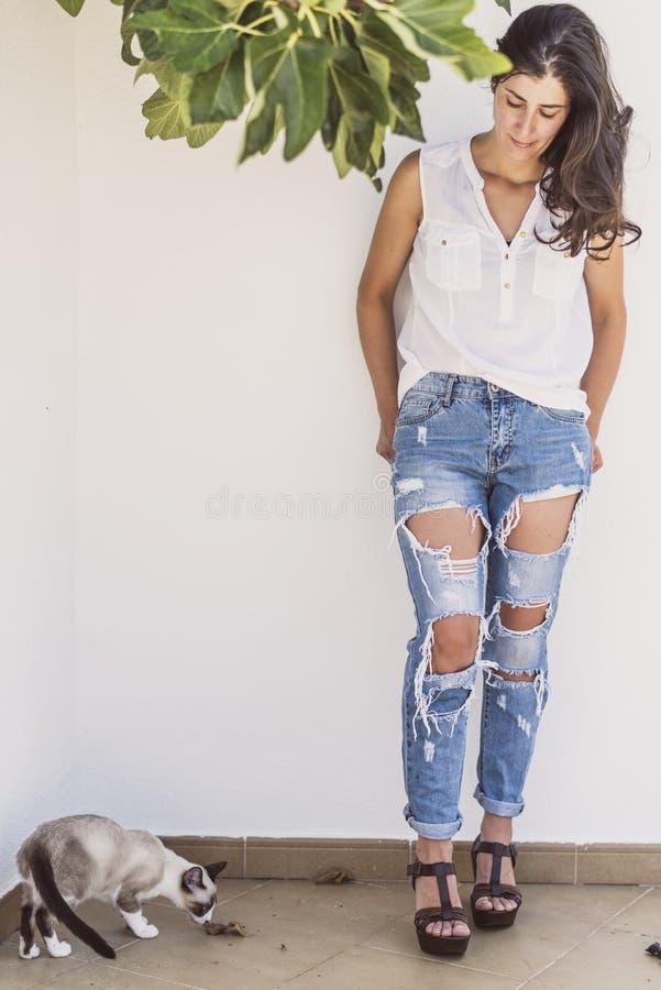 Vrij rijpe vrouw met moderne stijl met gebroken jeans en kat stock afbeeldingen