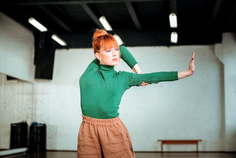 Vrij rood haired meisje in een groene col die zich in asana bevinden royalty-vrije stock foto's