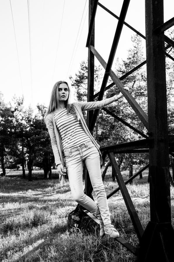 Vrij slank meisje die op de camera in park dichtbij de toren stellen stock foto's
