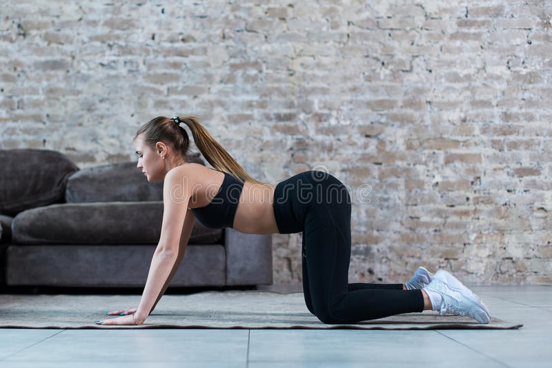 Vrij slanke sportvrouw het praktizeren gymnastiek die oefeningen doen die op alle fours zich binnen bevinden stock afbeeldingen