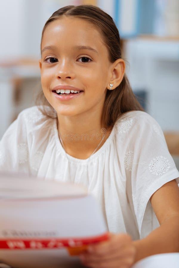 Vrij slim schoolmeisje die in een ruimte bestuderen stock fotografie