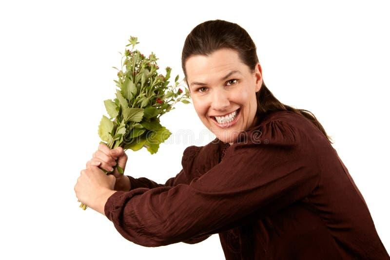 Vrij volwassen vrouw met bloemen die als honkbal worden gehouden royalty-vrije stock afbeelding