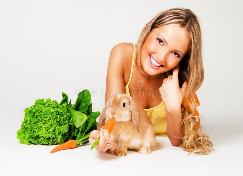 Vrij vrolijk meisje dat een konijn voedt stock foto's