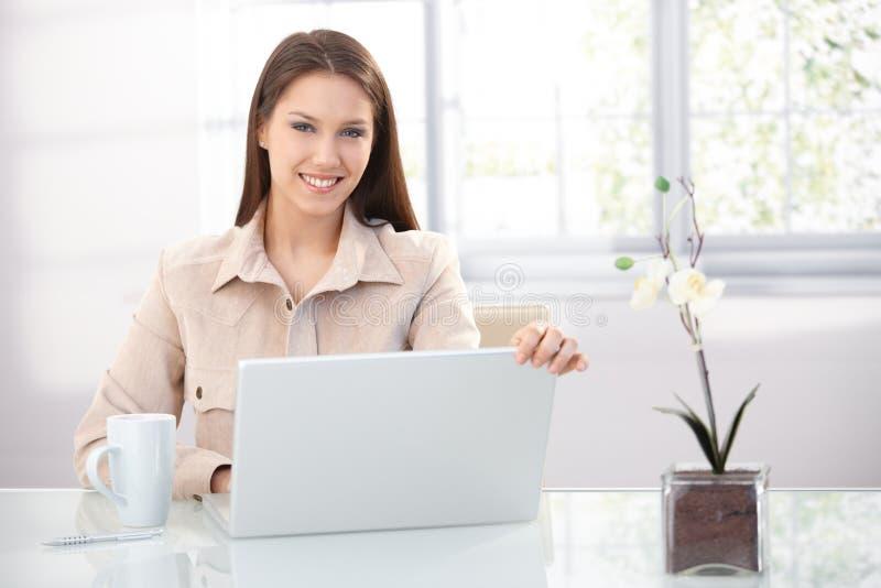Vrij vrouwelijk gebruikend laptop die thuis glimlacht stock afbeelding