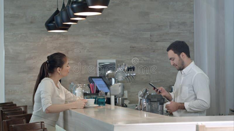 Vrij vrouwelijke klant die haar telefoonaantal geven aan knappe barista royalty-vrije stock afbeelding