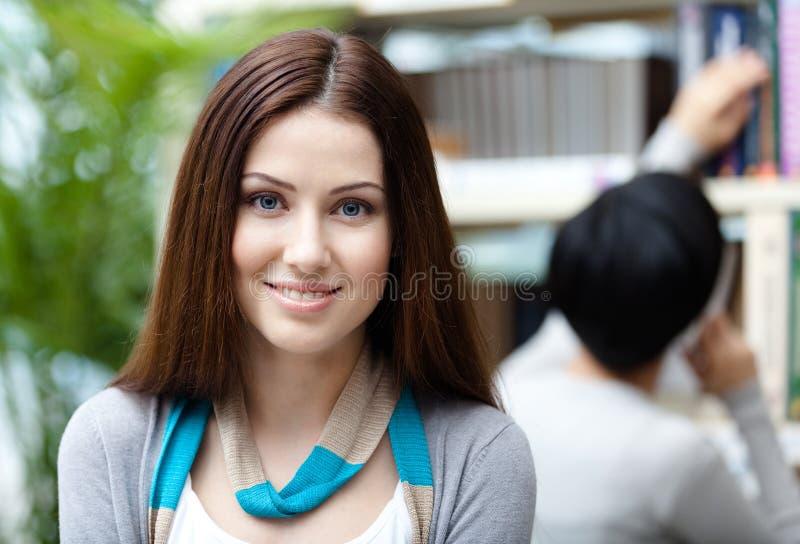 Vrij vrouwelijke student bij de bibliotheek tegen boekenrekken royalty-vrije stock foto