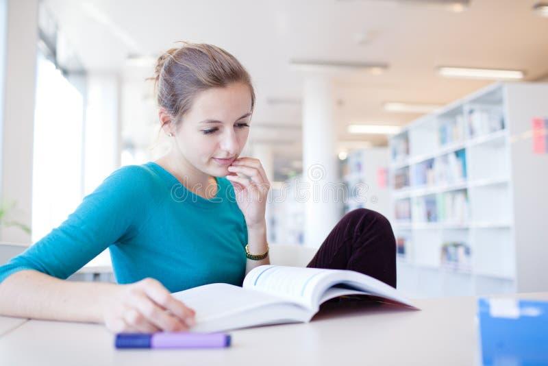 Vrij vrouwelijke student in een bibliotheek stock foto
