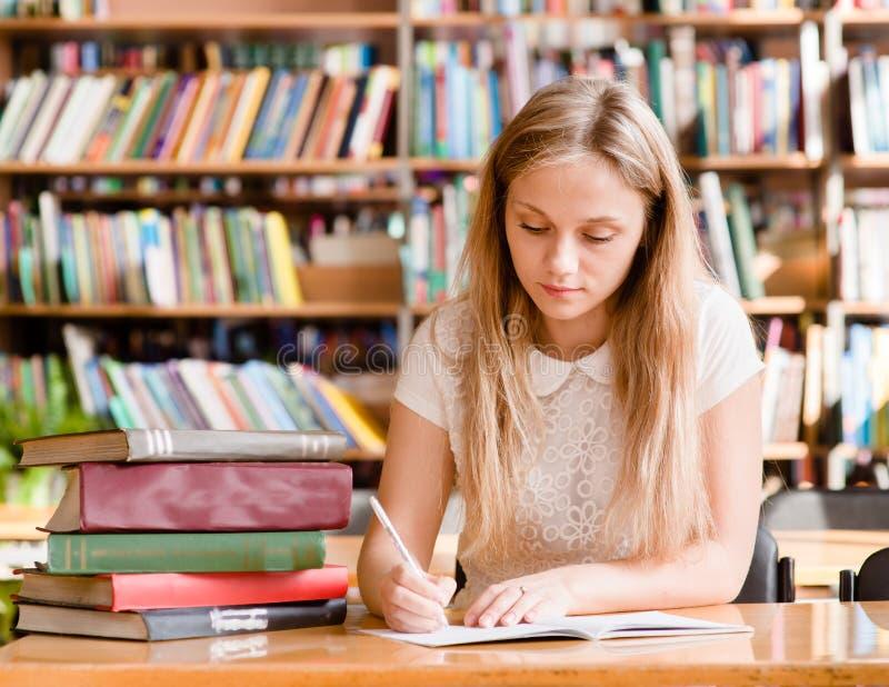 Vrij vrouwelijke student met boeken die in een middelbare schoolbibliotheek werken stock foto's