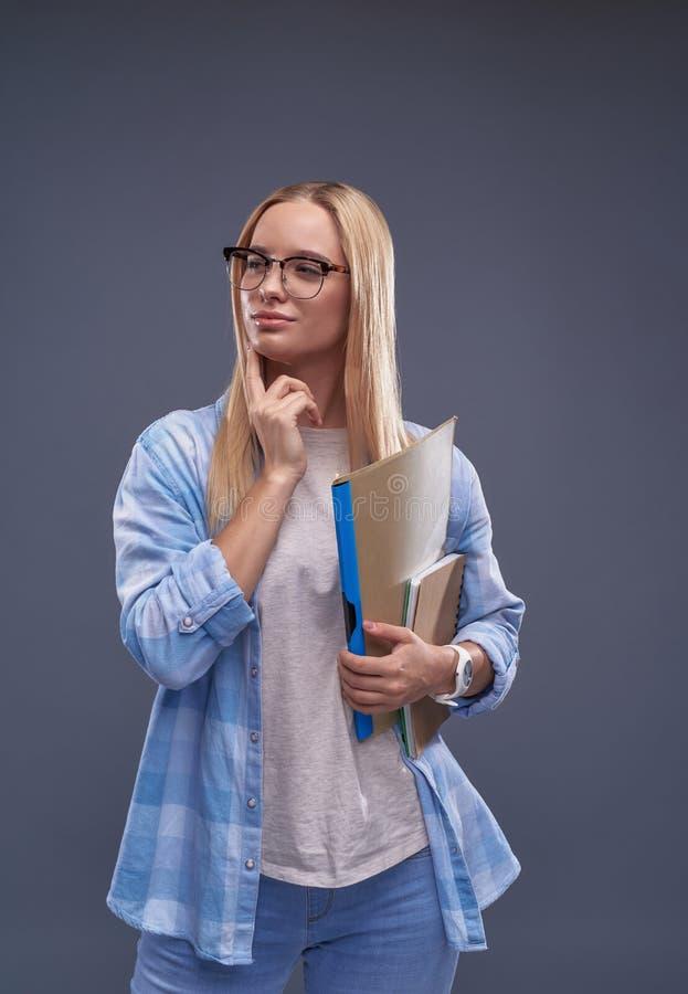 Vrij zelfverzekerd meisje met documenten die zich tegen blauw-grijze achtergrond bevinden stock afbeeldingen